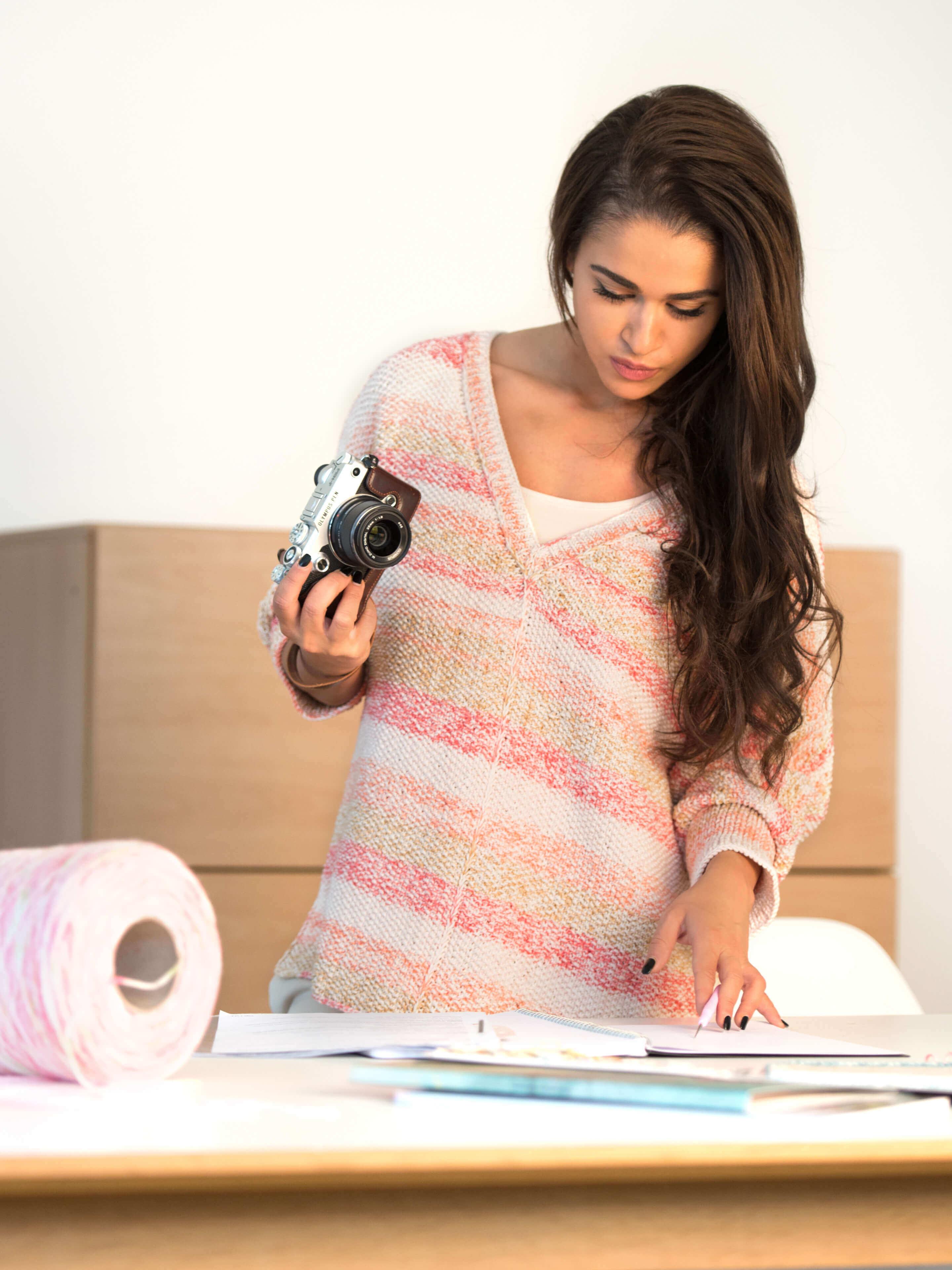 Frau mit Fotoapparat und gestricktem Pullover in Pastellfarben