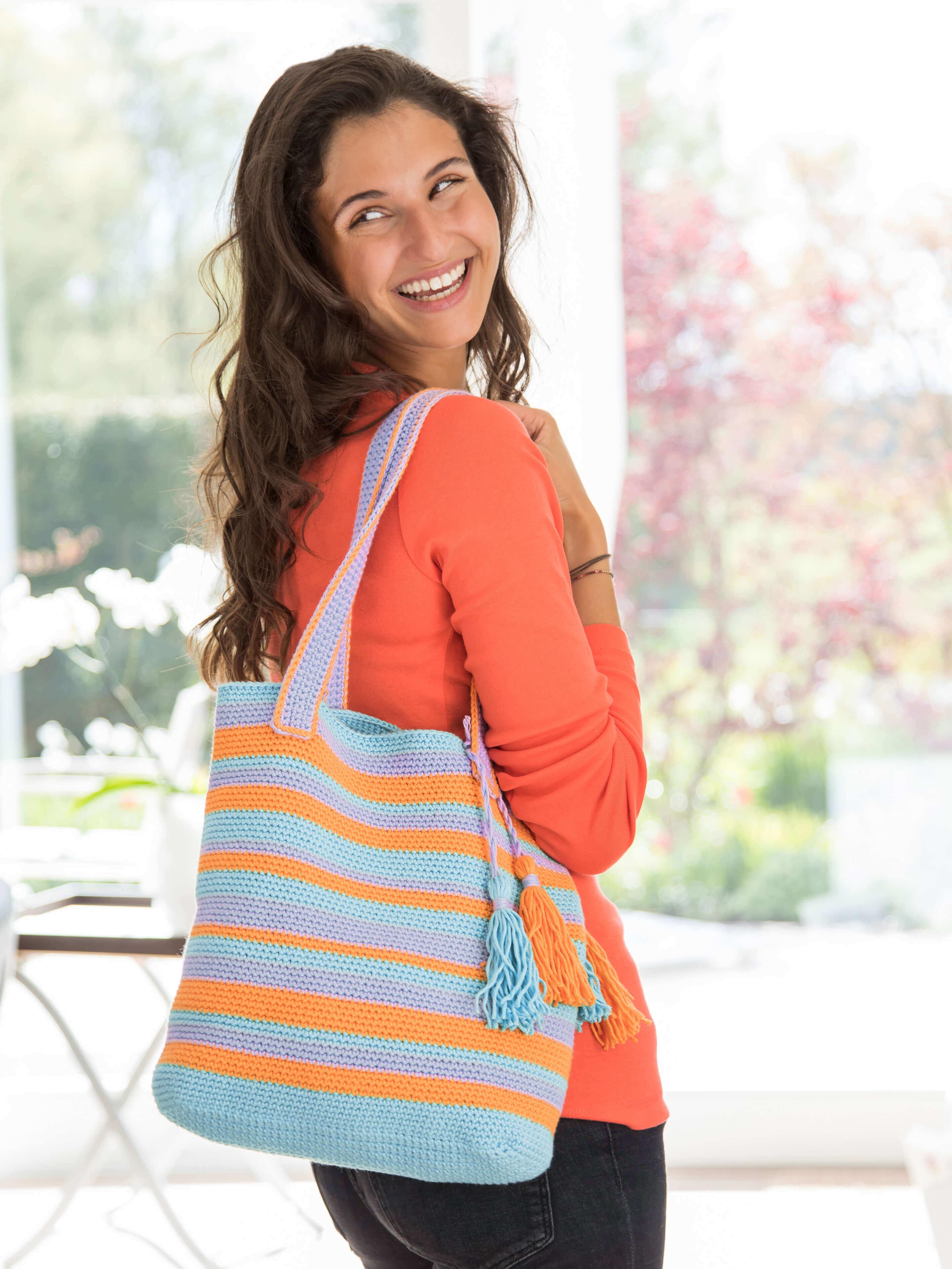 Frau mit gehäkelter Einkaufstasche in orange-lila-blau