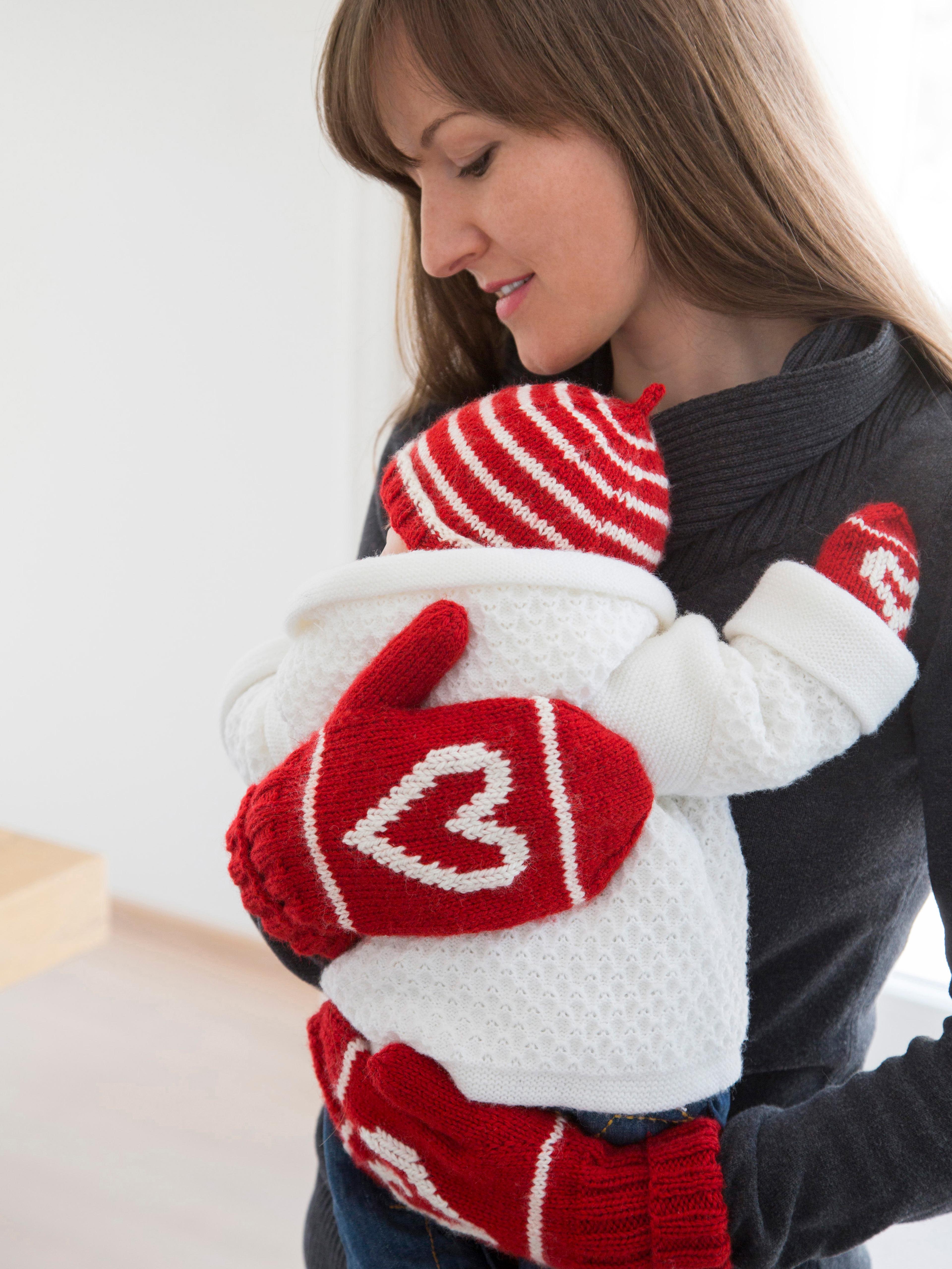 Mutter mit Baby mit gestrickter Babykleidung in rot-weiß