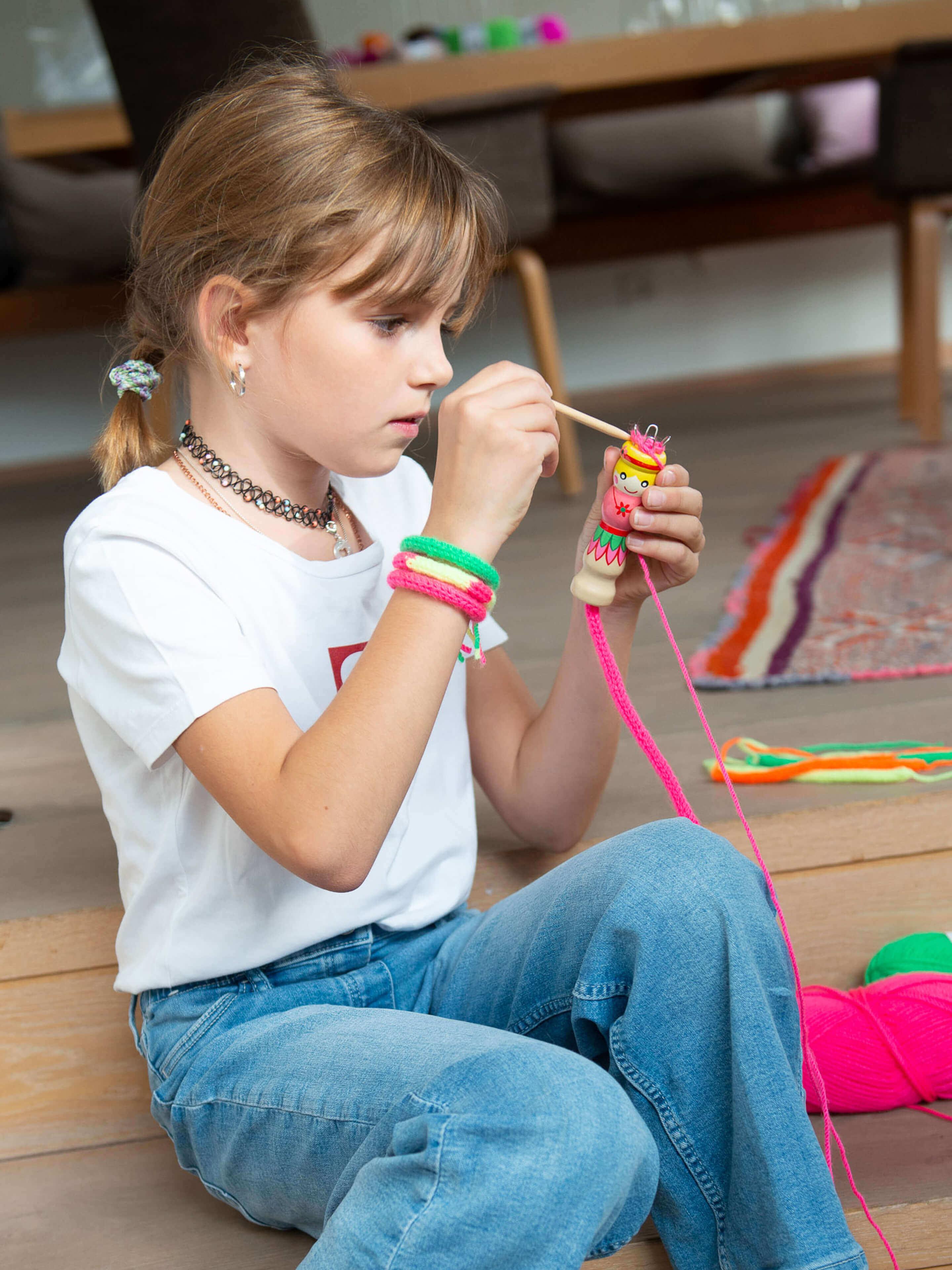 Mädchen strickt mit Strickliesel